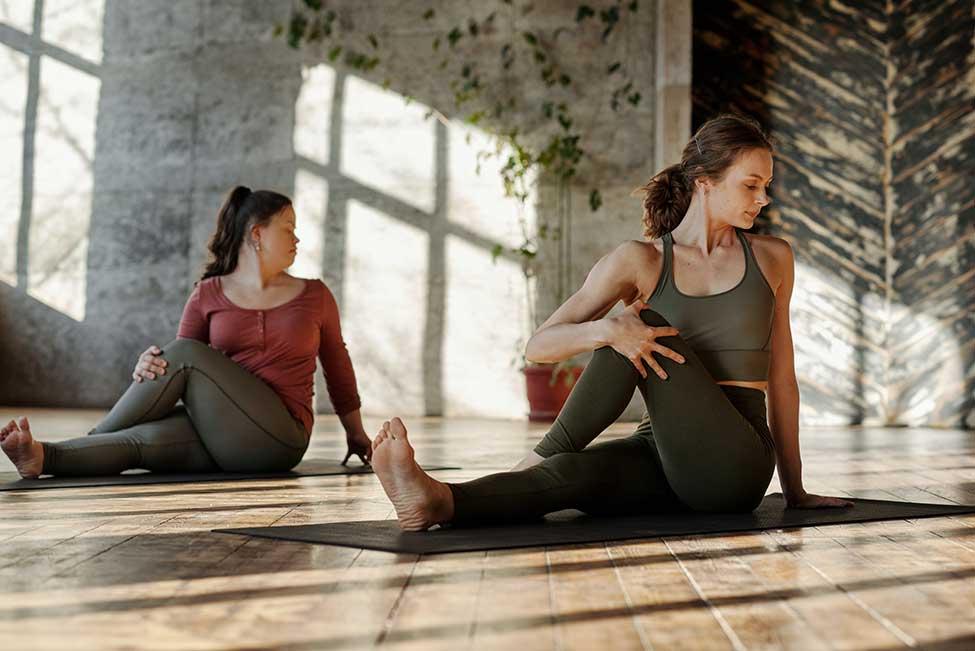 Two women doing yoga in the sunlight