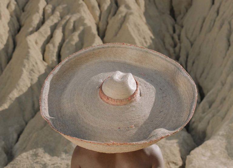 Woman wearing sun hat facing black rock desert