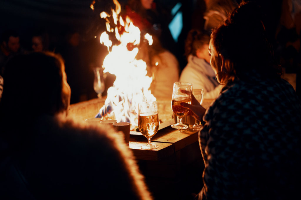 Group of people huddled around a fire pit drinking cocktails